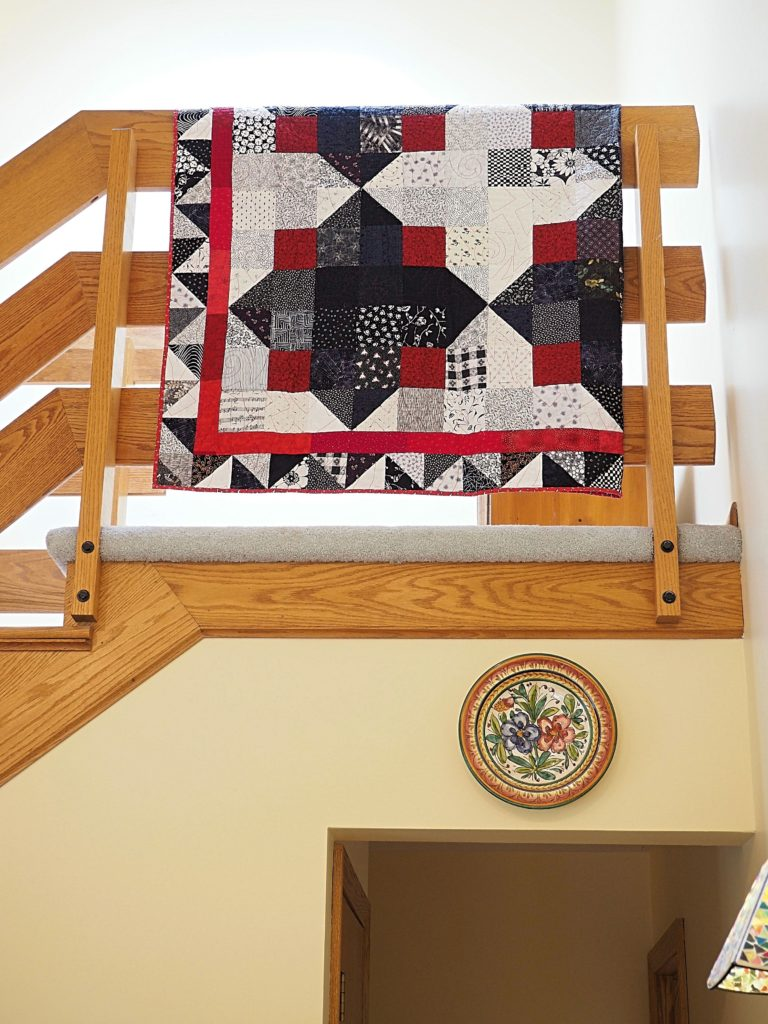 Save money and use the railings around your house to display quilts.