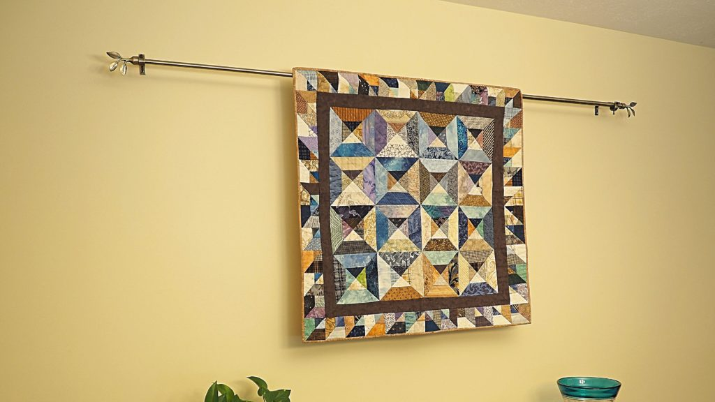A curtain rod is an unexpected and practical method to show off quilts.