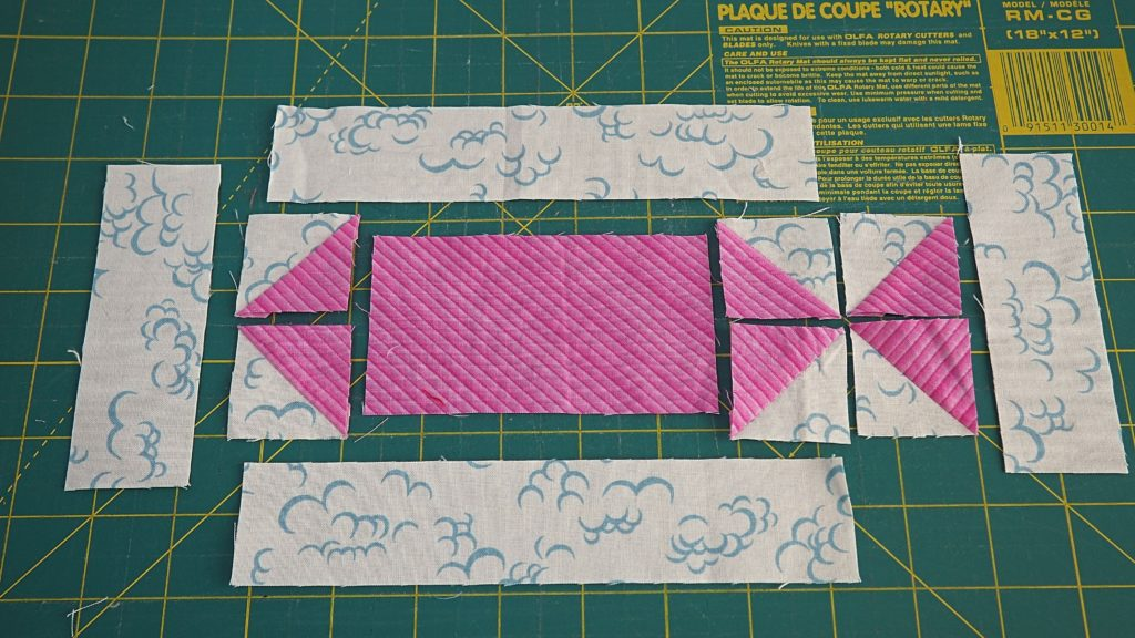 Laying out the scrappy swimming fish quilt block